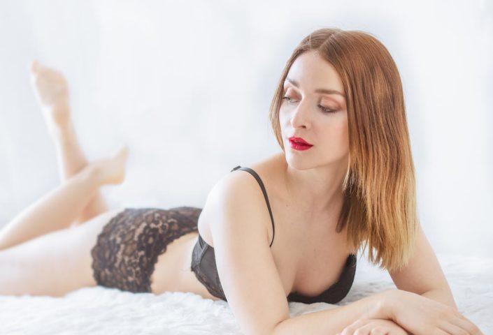 portrait de femme boudoir allongée sur un li en lingerie